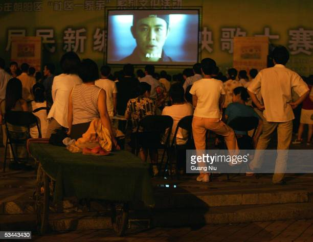 People watch a free movie by an openair cinema at a residential area August 20 2005 in Beijing China The event is aimed at promoting local film...
