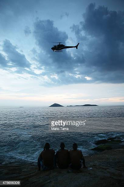People watch a helicopter pass over Arpoador at the beginning of the Vem Ni Mim Que Sou Facinha street carnival bloco on February 28 2014 in Rio de...