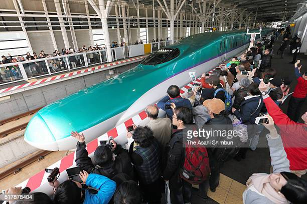 People watch a Hokkaido shinkansen bullet train 'Hayabusa 22' departing for Tokyo at the JR Hakodate Hokuto Station on March 26 2016 in Hokuto...