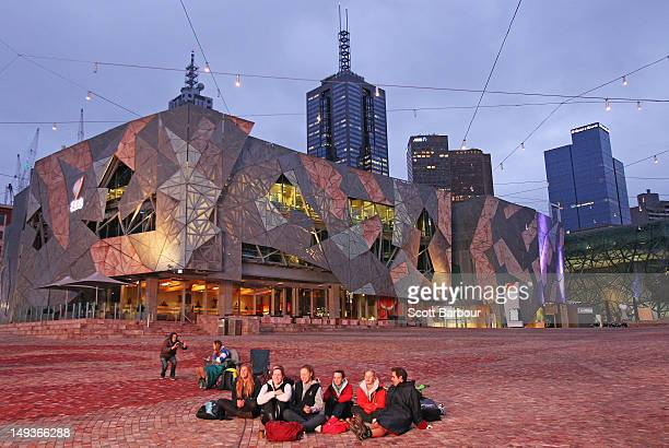 People watch a large screen showing the Opening Ceremony of the 2012 London Olympic Games at Federation Square on July 28 2012 in Melbourne Australia
