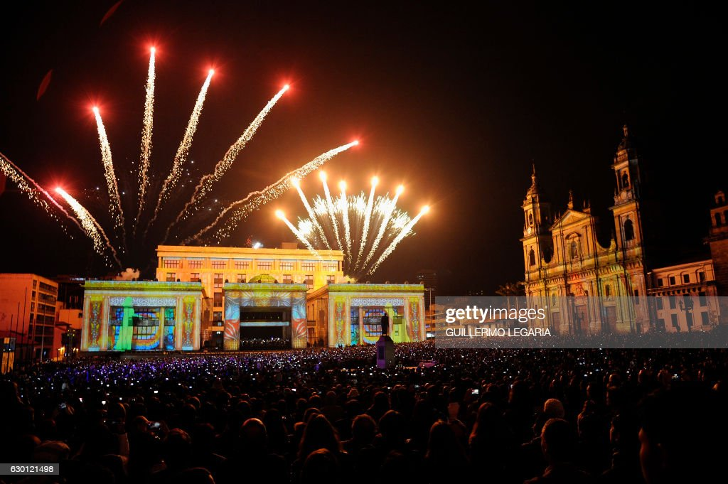 People watch a light and fireworks show of the 'Fete des Lumieres de Lyon' in the Bolivar square of Bogota, Colombia on December 16, 2016, for the launch of the France-Colombia Year 2017