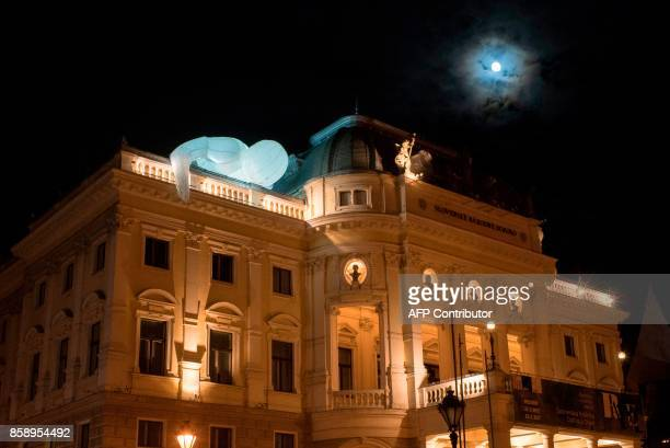 People watch a light object titled 'Humanoid 2' by Amanda Parer of Australia displayed at the Slovak National Theatre in Bratislava during the White...