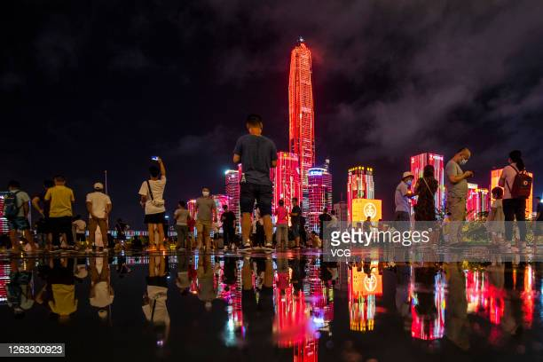 People watch a light show performed on buildings around Shenzhen Citizen Center to celebrate China's Army Day on August 1 2020 in Shenzhen Guangdong...