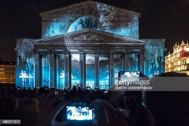 People watch a light show projected on the facade of the Bolshoi Theatre in Moscow on September 26 during the 'Circle of Light' Moscow International...