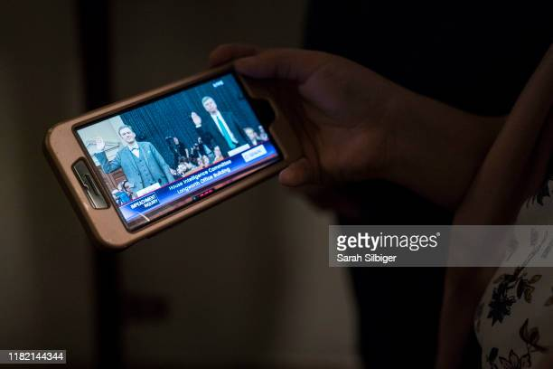 People watch a live stream coverage in the hallways of the Longworth House Office Building as Amb William Taylor And Deputy Assistant Secretary Of...