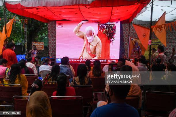 People watch a live telecast on a screen from Ayodhya of India's Prime Minister Narendra Modi taking part in a Hindu religious ritual during a...