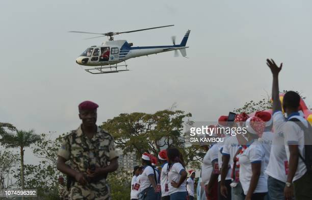 People watch a man dressed as Santa Claus waving from a helicopter as he arrives at the presidential palace in Abidjan on December 22 during a...