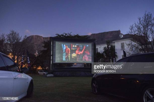 People watch a movie from their car at the Galileo drivein being held on a school sports field in Cape Town with Table Mountain in the background on...