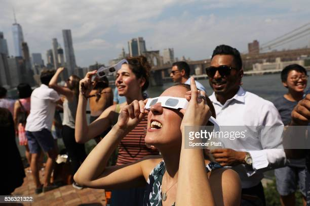 People watch a partial solar eclipse from the roof deck at the 1 Hotel Brooklyn Bridge on August 21 2017 in the Brooklyn borough of New York City...