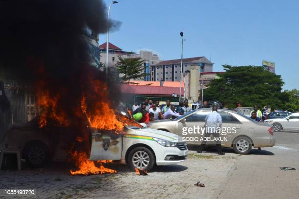 People watch a police vehicle as it goes up in flames following clashes with supporters of Islamic Movement of Nigeria protesting against the...