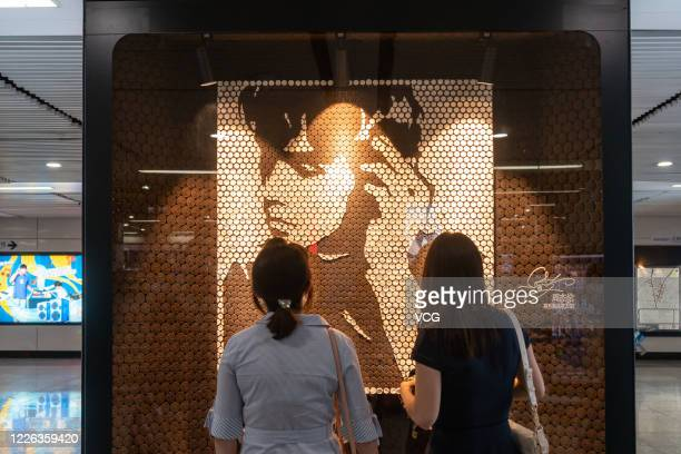 People watch a portrait of singer Jay Chou, which is made up of Oreo Cookies, during an Oreo Art Exhibition at Xujiahui Subway Station on May 21,...