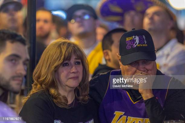 People watch a pregame tribute to Kobe Bryant on televisions in a restaurant near Staples Center as the first Lakers game since the former NBA star...