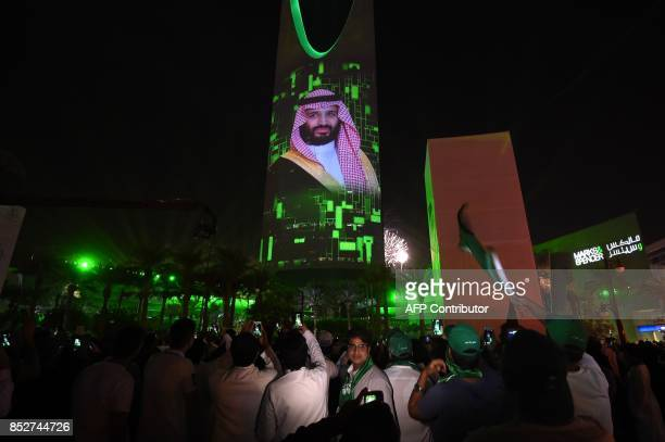 People watch a projection depicting a portrait of Crown Prince Mohammed bin Salman during an event in the capital Riyadh on late September 23 2017...