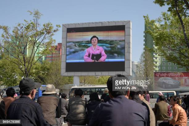 TOPSHOT People watch a public television screen showing coverage of the 'Third Plenary Meeting' of the 7th central committee of the ruling Workers'...