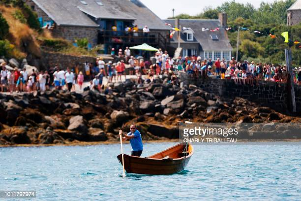 People watch a race of a scull boat also called godille in French during the Regates de Chausey on the Island of Chausey off the coastal town of...