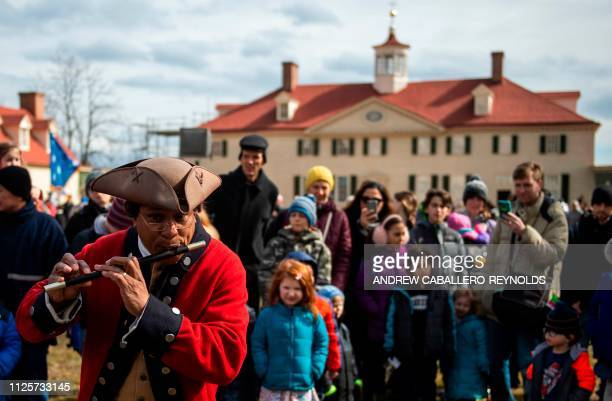 People watch a reenactor play the flute as part of Presidents day events at George Washingtons' Mount Vernon estate in Mt Vernon Virginia on February...