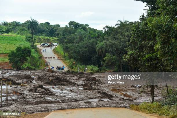 People watch a road buried in mining waste a day after the collapse of a dam from an ironore mine belonging to Brazil's mining company Vale in...