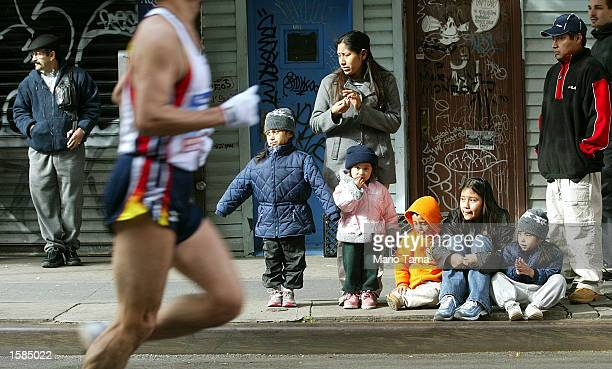 People watch a runner pass in Brooklyn during the New York City Marathon November 3 2002 in New York City Joyce Chepchumba and Rodgers Rop both from...