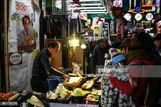People watch a salesman demonstrate a kitchen implement as he sells his wares in Ameya Yokocho market on January 4 2018 in Tokyo Japan Ameya Yokocho...