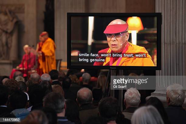 People watch a screen displaying subtitles as His Holiness the Dalai Lama addresses the audience in St Paul's Cathedral after receiving the 2012...