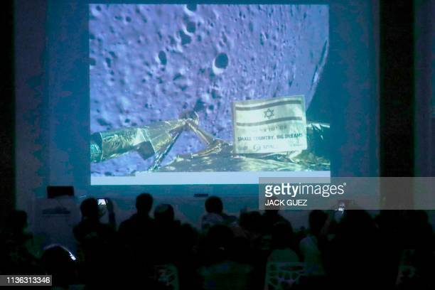People watch a screen showing a picture taken by the camera of the Israel Beresheet spacecraft of the moon surface as the craft approaches and before...