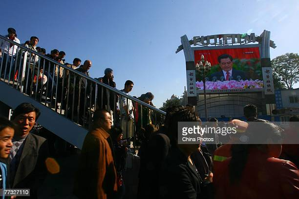 People watch a screen showing Chinese President Hu Jintao delivering a speech during opening ceremony the 17th National Congress of the Communist...