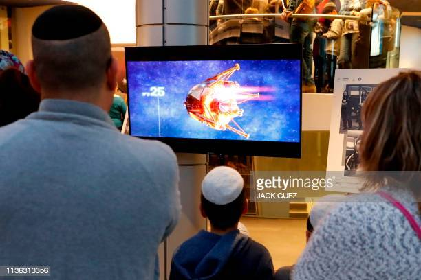 TOPSHOT People watch a screen showing explanations of the landing of Israeli spacecraft Beresheet's at the Planetaya Planetarium in the Israeli city...