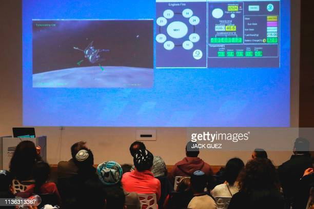 People watch a screen showing explanations of the landing of Israeli spacecraft Beresheet's at the Planetaya Planetarium in the Israeli city of...