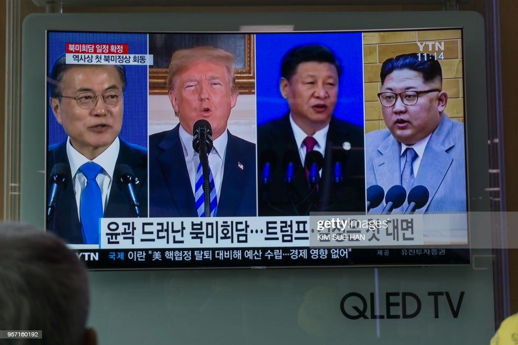 People watch a screen showing images of (L-R) South Korea's president Moon Jae-in, US president Donald Trump, China's president Xi Jinping, and North Korea's leader Kim Jong Un at a railway station in Seoul on May 11, 2018. - Donald Trump on April 10 revealed his historic summit with Kim Jong Un -- the first-ever between a sitting US president and a North Korean leader -- will take place in Singapore on June 12.