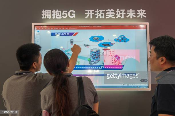 People watch a screen showing information on 5G technology during the Mobile World Conference in Shanghai on June 27 2018 / China OUT