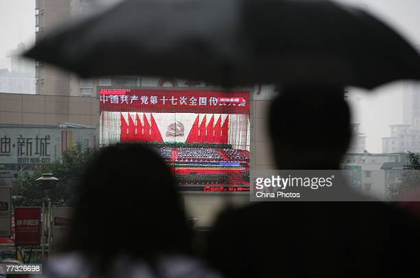 People watch a screen showing the opening ceremony the 17th National Congress of the Communist Party of China in rain on October 15, 2007 in...