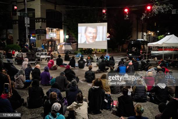 People watch a screening of 13th, a documentary film by director Ava DuVernay, in an intersection outside of the Seattle Police Departments East...