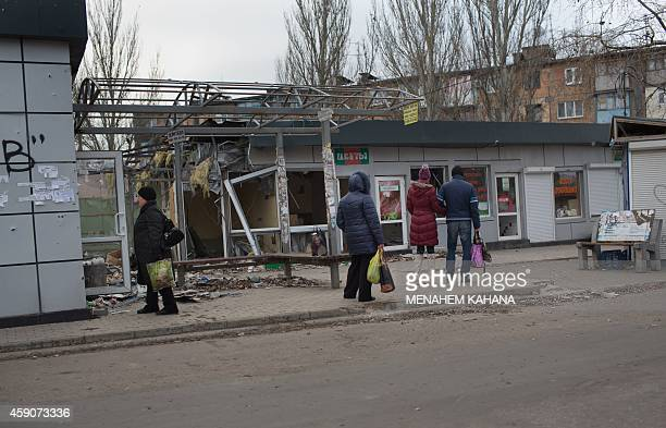 People watch a shop damaged by shells at Oktyabrskiy district in the city of Donetsk on November 16 2014 as artillery fire continues to rock the...