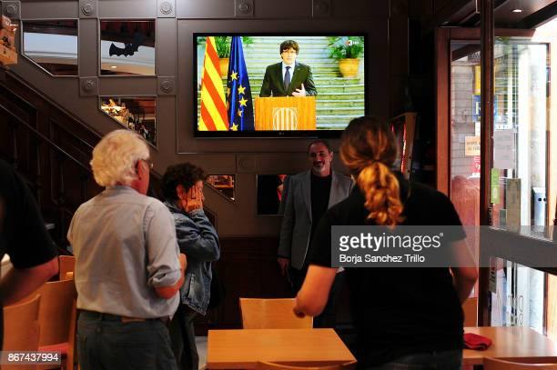 People watch a speech by Carles Puigdemont on local TV channel in a restaurant near to to Palau Catalan Regional Government building on October 28...