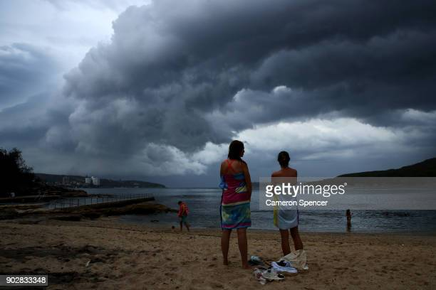 People watch a storm front cross Sydney Harbour at Fairlight Beach on January 9 2018 in Sydney Australia Heavy wind rain and severe hailstorms are...