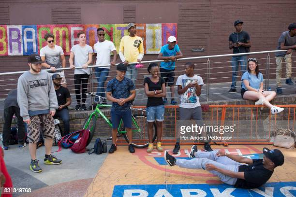 People watch a street dance performance on March 19 2016 in Braamfontein in downtown Johannesburg South Africa The area a culture hub with many...