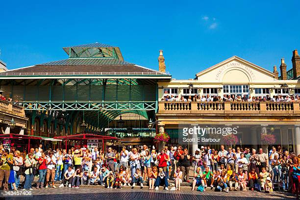 People watch a street performer in Covent Garden
