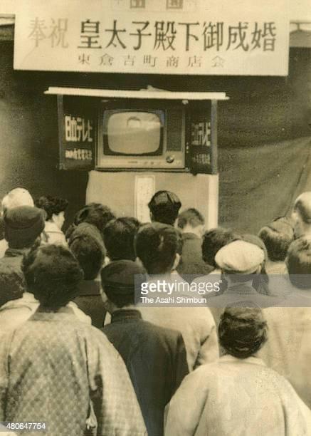 People watch a street television reporting the royal wedding of the Crown Prince Akihito and Michiko Shoda at Higashi Kurayoshi Shopping Street on...