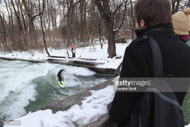 People watch a surfer riding the Eisbach wave on January 23 2013 in Munich Germany