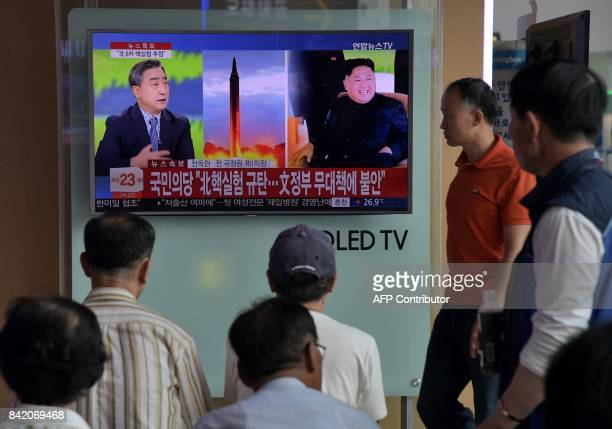 People watch a television display at a train station in Seoul on September 3, 2017 showing a news broadcast about North Korea's latest possible...