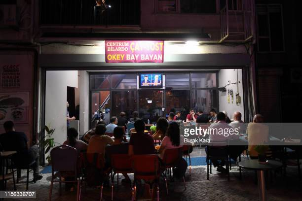 People watch a television in a cafe as Istanbul mayoral candidate Binali Yildirim of the ruling Justice and Development Party and Istanbul mayoral...