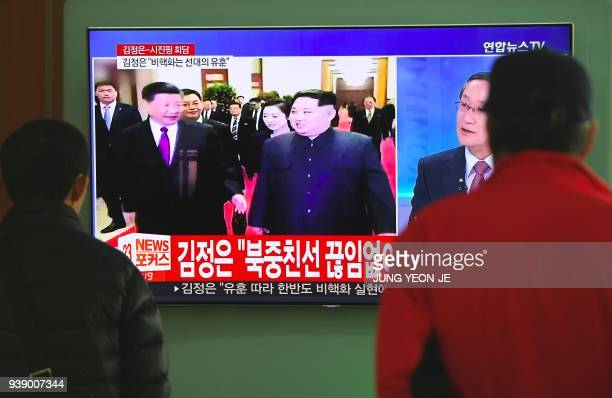 People watch a television news about a visit to China by North Korean leader Kim Jong Un at a railway station in Seoul on March 28 2018 North Korea's...