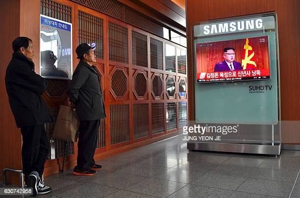People watch a television news broadcast at a railway station in Seoul on January 1, 2017 showing North Korean leader Kim Jong-Un's New Year's...