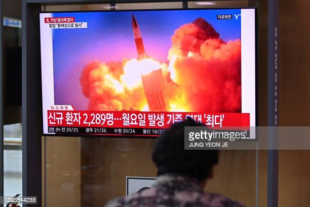 People watch a television news broadcast showing file footage of a North Korean missile test, at a railway station in Seoul on September 28 after...