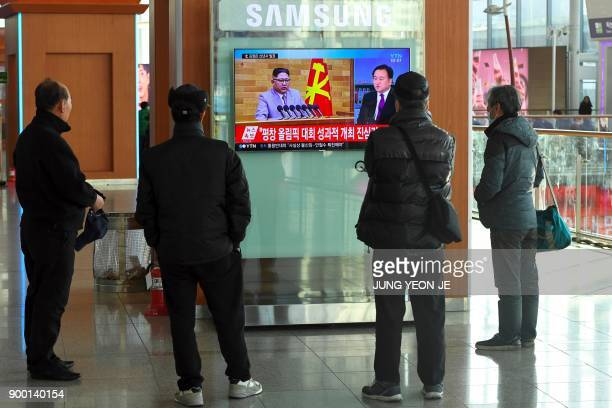 People watch a television news broadcast showing North Korean leader Kim JongUn's New Year's speech at a railway station in Seoul on January 1 2018...