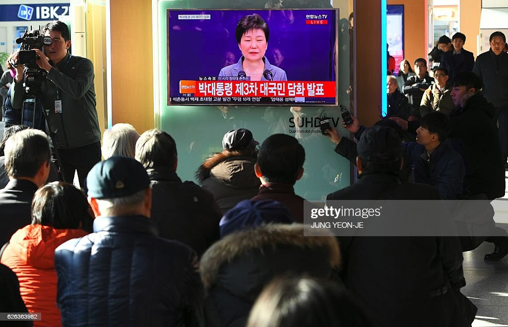 People watch a television news live showing South Korean President Park Geun-Hye making a speech, at a railway station in Seoul on November 29, 2016. South Korea's scandal-hit President Park Geun-Hye said on November 29 she was willing to leave office before the end of her official term early 2018 and would let parliament decide on her fate. / AFP / JUNG Yeon-Je