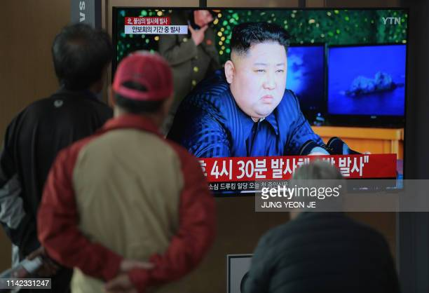 People watch a television news programme showing a picture of North Korean leader Kim Jong Un at a railway station in Seoul on May 9 2019 North Korea...