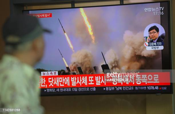 TOPSHOT People watch a television news programme showing file footage of North Korea's projectile weapons at a railway station in Seoul on May 9 2019...