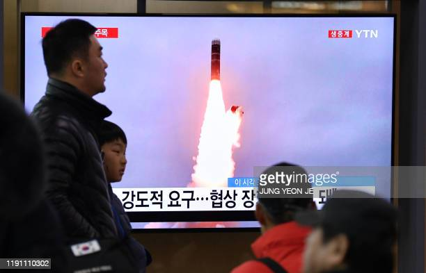 People watch a television news programme showing file footage of North Korea's missile test, at a railway station in Seoul on January 1, 2020. -...