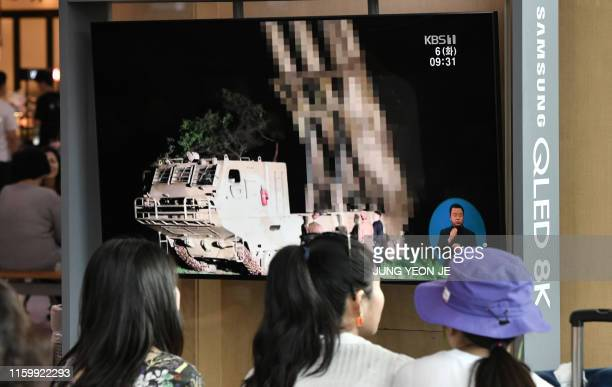 People watch a television news screen showing a file footage of North Korea's missile launch at a railway station in Seoul on August 6 2019 North...